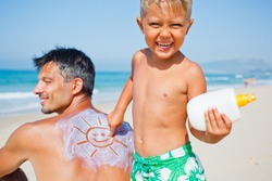 Adorable boy at tropical beach applying sunblock cream on a father's back.