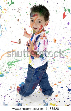 Adorable boy covered in paint splatter on wall floor and self