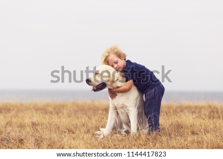 adorable boy hugging her labrador retriever. happy kid with big white dog outdoors. child and his dog best friend having fun in the garden. toddler boy with cute family dog.  #1144417823