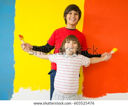 Adorable boy in bright paint with mess of paint child on wall #603525476