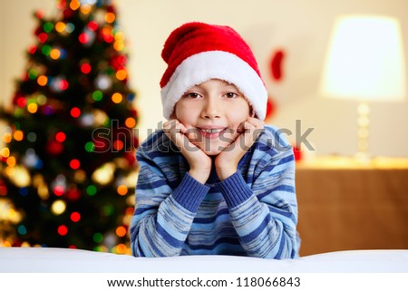 Adorable boy in Santa hat smiling and looking at camera