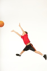 Adorable boy jumping and catching basketball ball