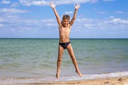 Adorable boy jumping on the beach against blue sky