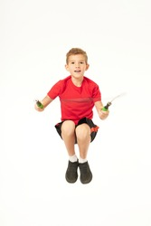 Adorable boy jumping over skipping rope in the air