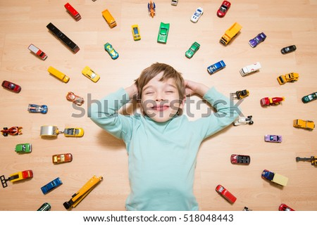 Adorable boy lying on the ground and dreaming with toy cars around