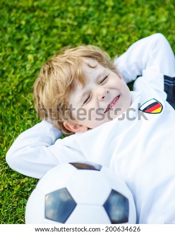 Adorable boy of 4 resting after playing soccer with football on football field, outdoors.