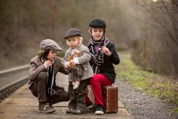 Adorable boy on a railway station, waiting for the train with suitcase and beautiful vintage porcelain doll