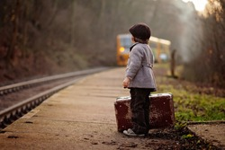 Adorable boy on a railway station, waiting for the train with suitcase and teddy bear, vintage look