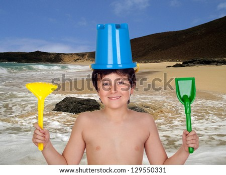 Adorable boy playing with toy for the beach in the sea - stock photo