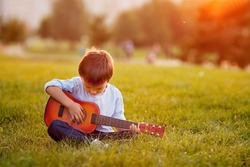 Adorable boy with guitar, sitting on the grass on sunset