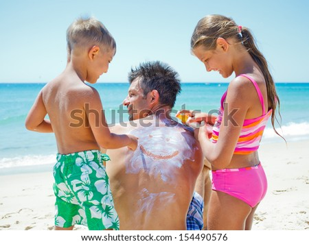 Adorable boy with his sister at tropical beach applying sunblock cream on a father's back.