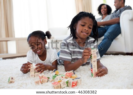 Adorable brother and sister playing alphabetic cubes lying on the floor