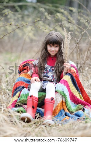 Adorable brunette little girl with very long hair in colorful dress and  red rain boots in the field with colorful stripe blanket