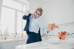 Adorable busy attractive charming beautiful smiling lady office executive worker wearing spectacles in hurry early in the morning talking on the phone having a drink and croissant in kitchen