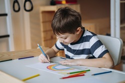 adorable caucasian boy of elementary age drawing a rainbow with pencils sitting at the desk in his room at home. Image with selective focus