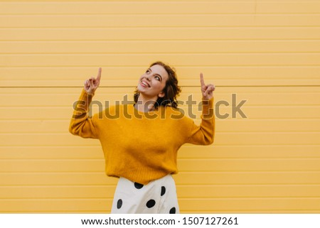 Adorable caucasian woman in stylish sweater having fun in autumn. Cheerful emotional girl with short hair posing on yellow background.