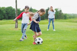 Adorable cheerful children playing soccer with ball on green grass