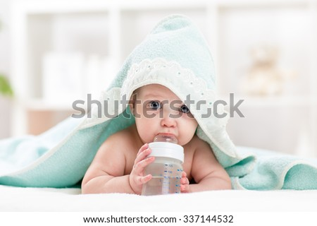 Adorable child baby drinking water from bottle. Little girl  wrapped bathing towel lying on bed.