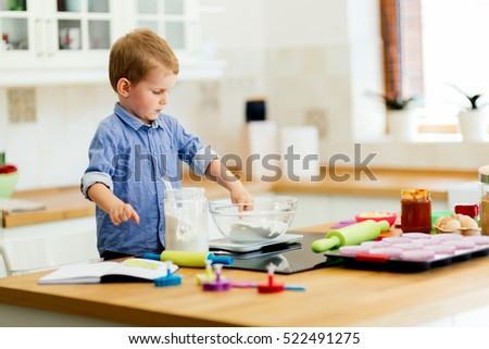 Adorable child below the age of 3  making cookies in kitchen