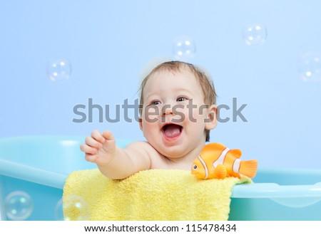 adorable child boy taking bath in blue tub