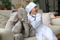Adorable child dressed as doctor playing with toy elephant, checking its breath with stethoscope.