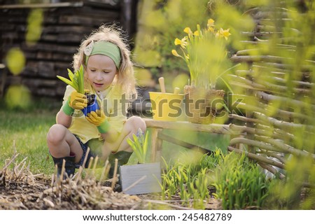 Adorable child girl in yellow cardigan and rubber gloves plays little gardener and planting flowers in spring garden