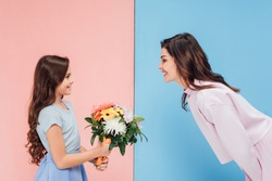 adorable child giving bouquet to attractive woman on blue and pink background