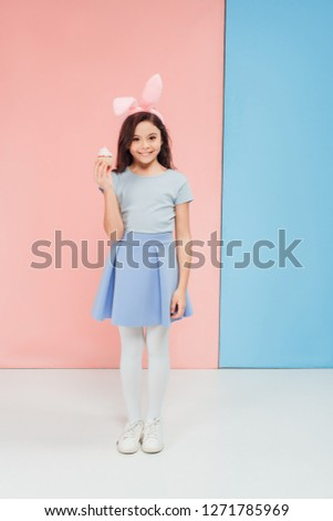 adorable child in easter bunny ears holding cupcake on blue and pink background