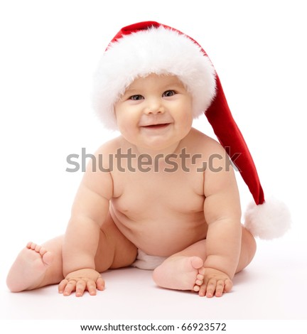 Adorable child is sitting on floor, wearing red Christmas cap, isolated over white