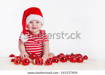 Adorable child is sitting on floor, wearing red Christmas cap, red balls around. isolated on white background