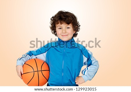 Adorable child playing the basketball with a orange background