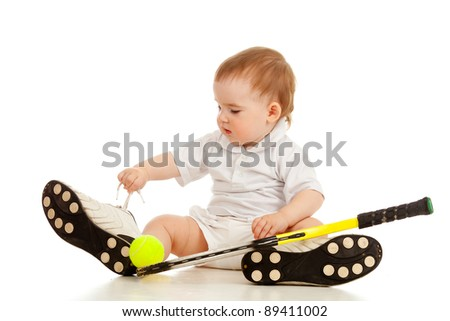 adorable child sitting on floor and playing with tennis racket and ball over white background