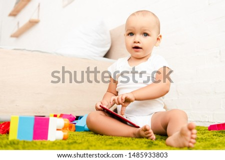 adorable child sitting on green floor and pointing with finger on digital device #1485933803