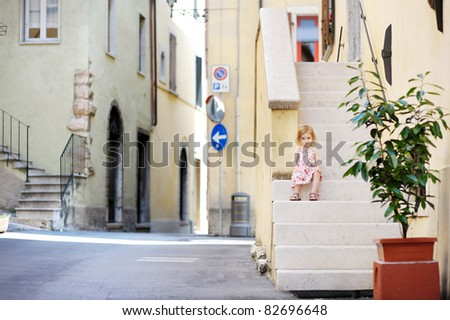 Adorable child sitting on the stairs in Italian town - stock photo