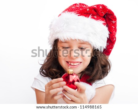 Adorable child wearing Santa Claus hat playing with a Christmas ball