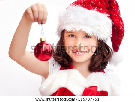 Adorable child wearing Santa Claus hat with a Christmas ball