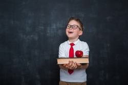 Adorable child whit books and apple in hands. Back to school. Education. Blackboard on background. Kid pupil boy in uniform. Happy child