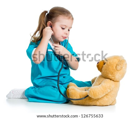 Adorable child with clothes of doctor playing and examining plush toy