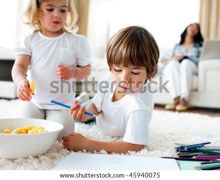 Adorable children eating chips and drawing lying on the floor