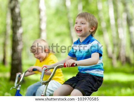 adorable children riding their bikes in park