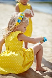 Adorable childs in dress posing outdoors. Little baby girls relaxing by the sea. Girls having fun together. Concept of summer,childhood and leisure
