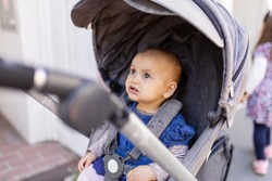Adorable concerned-looking baby looking up in gray stroller on the sidewalk. Portrait of cute infant in blue dress resting in stroller in the street. Peaceful toddlers outing