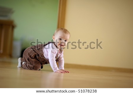 Adorable crawling baby girl at the floor