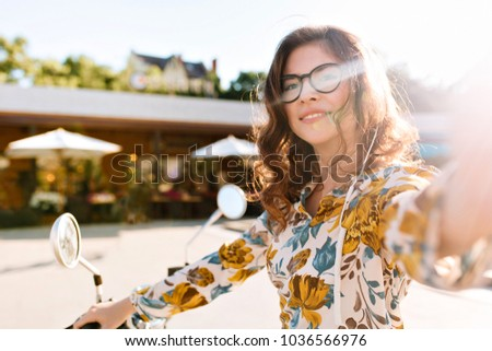 Adorable curly girl in trendy glasses making selfie during bike ride around town. Outdoor portrait of pretty young woman in stylish blouse with floral pattern enjoying sunlight in weekend. #1036566976