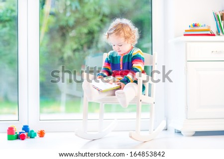 Adorable curly girl with curly hair wearing a colorful knitted dress reading in a white rocking chair next to a big window
