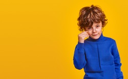 Adorable curly haired little nerd boy in blue casual sweater and eyeglasses looking at camera with curiosity while standing against yellow background