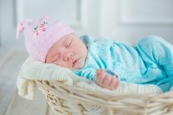 adorable cute baby girl sleeping in white basket on wooden floor