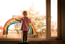 Adorable, cute, beautiful, happy preschool kid girl painting colorful rainbow on window, concept of joy and hope during pandemic and social distancing