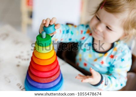 Adorable cute beautiful little baby girl playing with educational wooden rainbow toy pyramid #1055478674