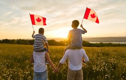 Adorable cute Caucasian boys holding Canadian flag on the father shoulder